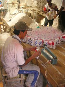Peruvians packaging salt for human consumption at the Salt Mines of Maras (Salinas de Maras), Cusco.